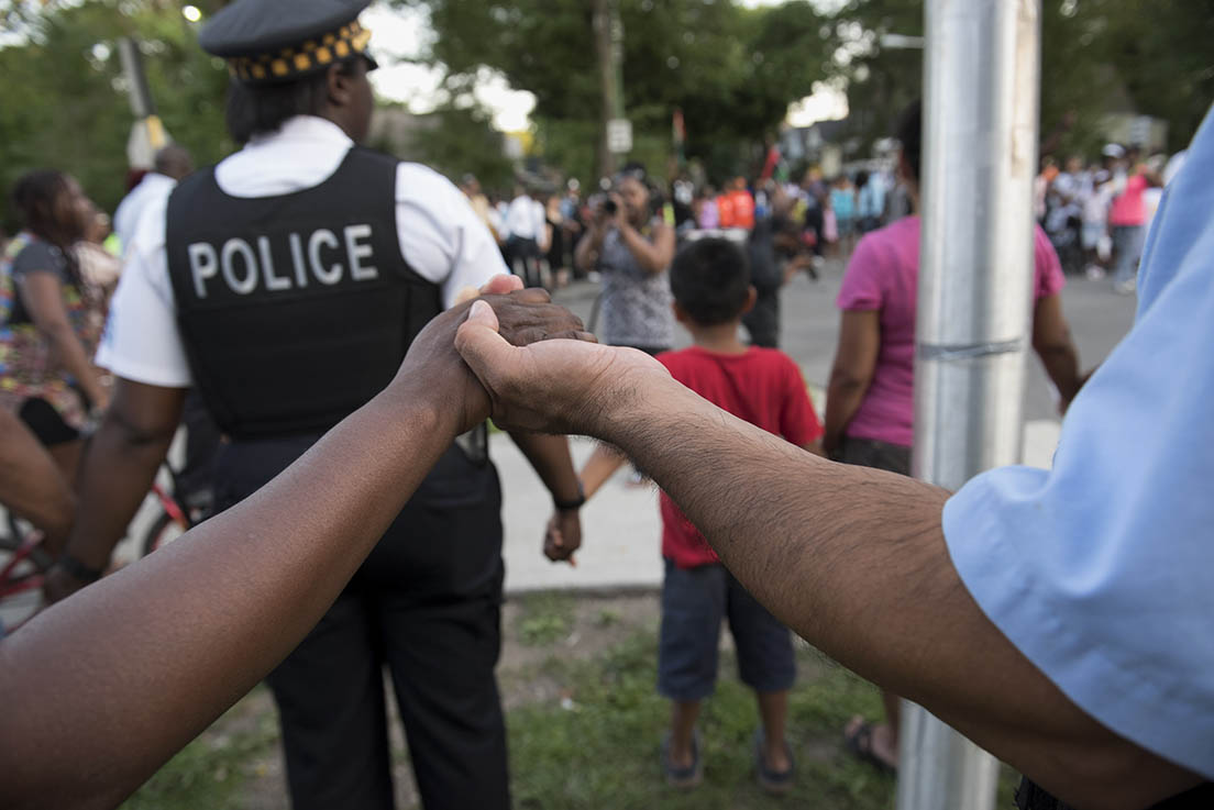 Image of residents and police officers of Chicago holding hands